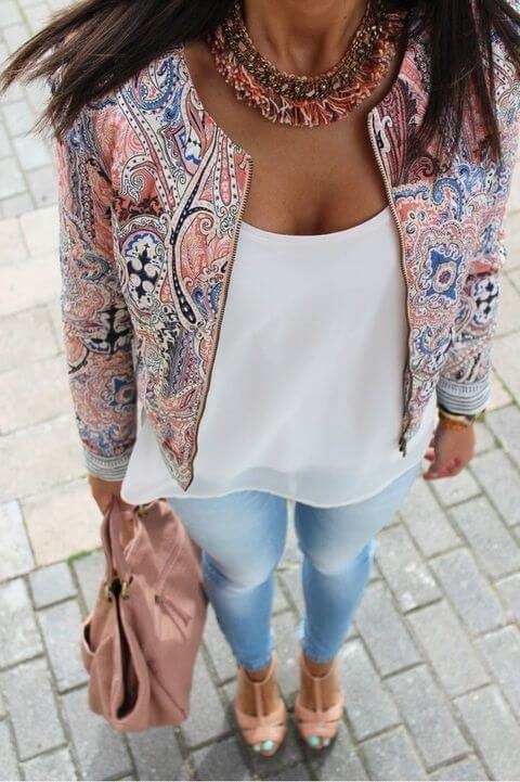 Chic brunette in skinny blue jeans and multi-colored patchwork jacket
