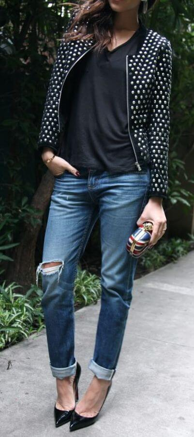 Chic brunette in studded jacket and ripped blue boyfriend jeans