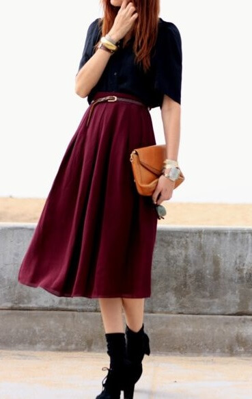 Chic redhead in burgundy midi woolen skirt and black blouse