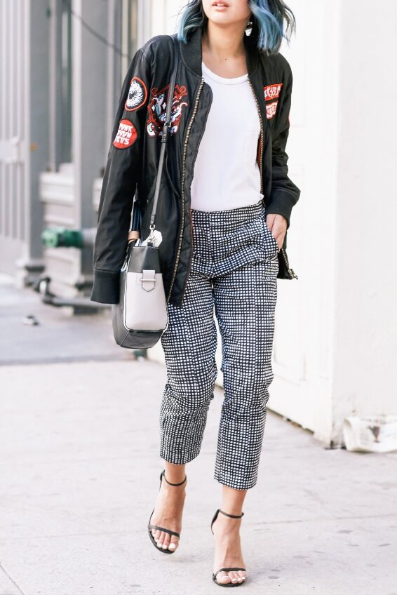Chic woman in grey pants, white vest, and black patchwork jacket