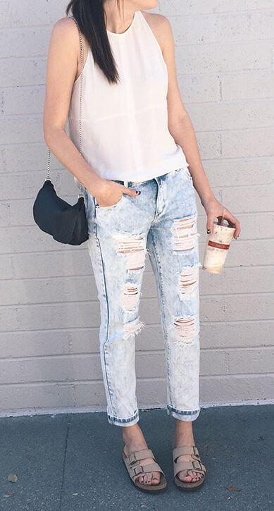Cute brunette in acid wash boyfriend jeans and Birkenstocks