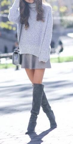 Cute brunette in grey turtleneck woolen sweater and grey woolen skirt