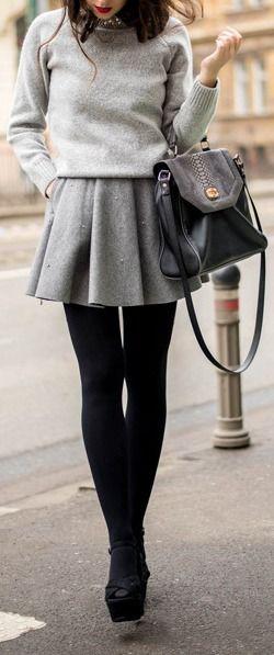 Cute brunette in grey woolen skirt and light grey woolen sweater