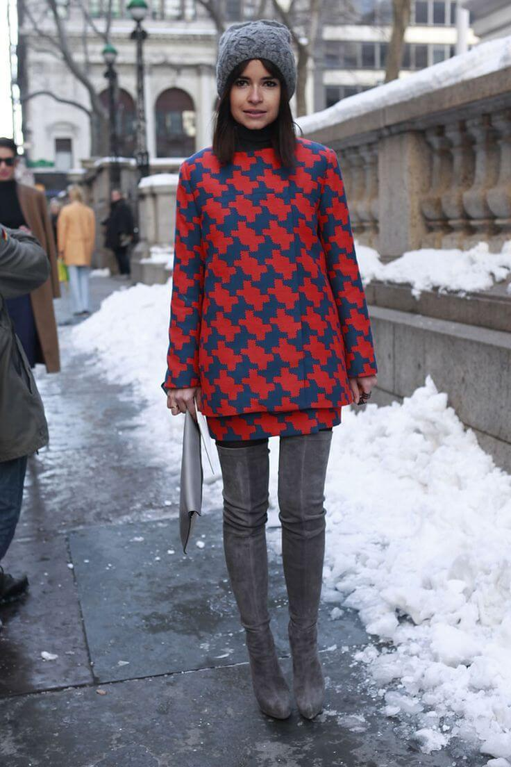 Miroslava Duma in a mod style printed dress, thigh high boots, and a knit beanie