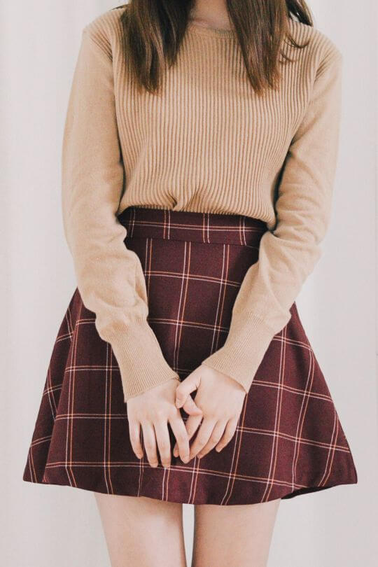 Model in a light cream sweater and a skater skirt