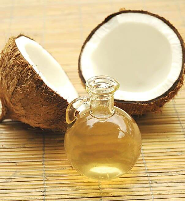 picture of a coconut cut in half next to a jar of oil
