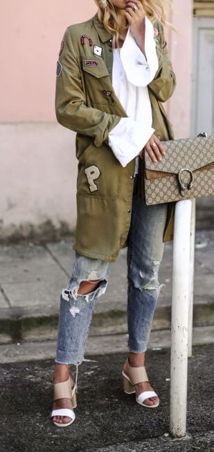 Stylish blonde in khaki patchwork parka jacket and ripped boyfriend jeans