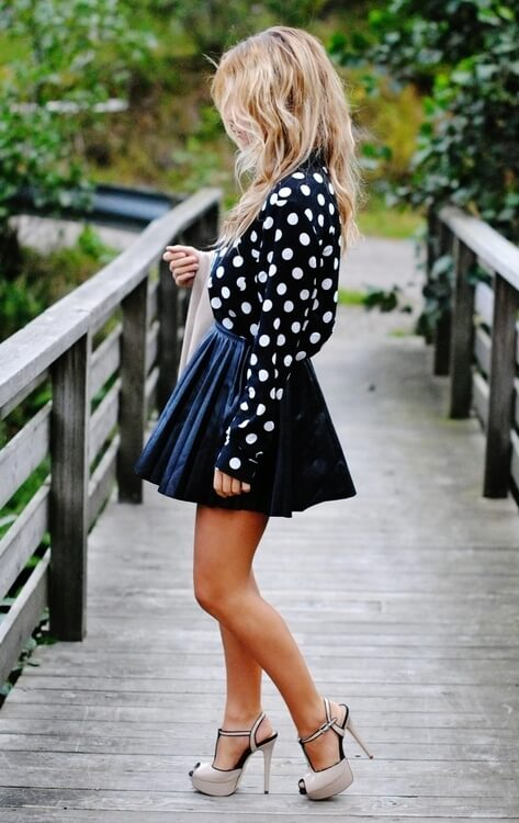 Stylish blonde in woolen mini skirt and polka dot blouse