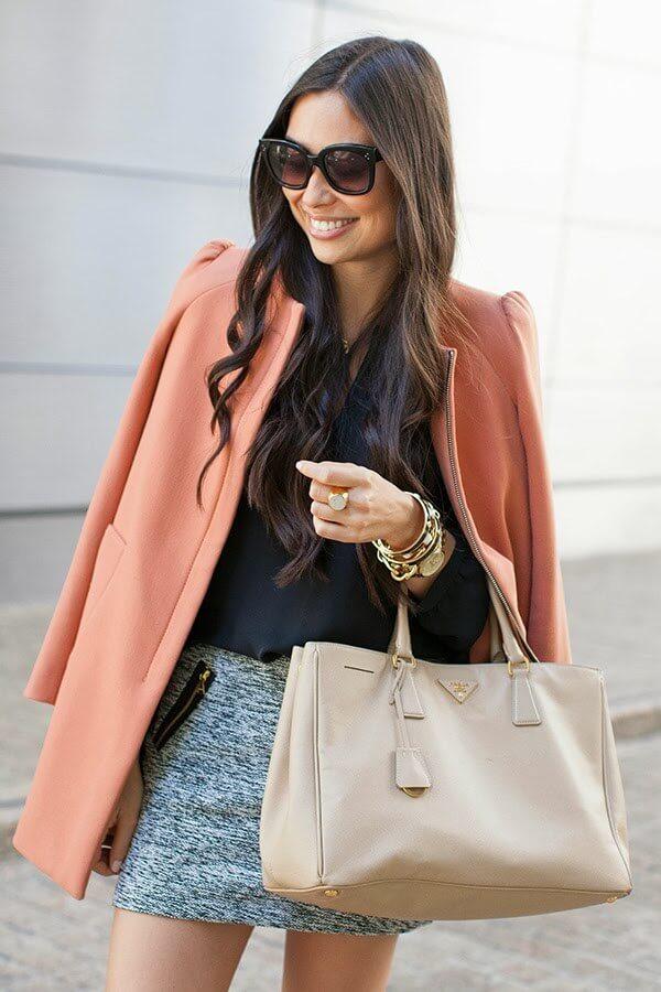 Stylish brunette in grey tweed woolen skirt and coral blazer