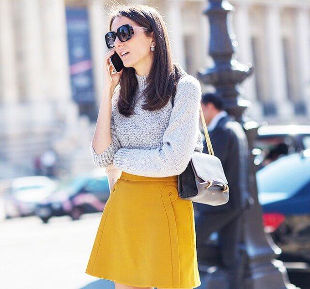 Stylish brunette in mustard woolen skirt and grey woolen sweater