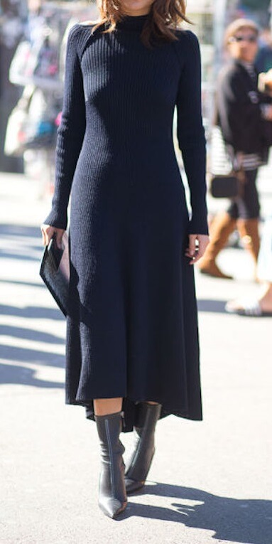 Stylish brunette in navy blue woolen dress and black leather boots