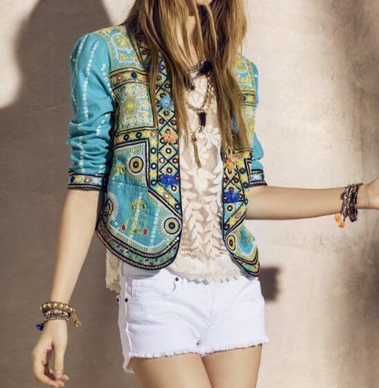 Stylish woman in turquoise patchwork jacket and white denim cut-off shorts