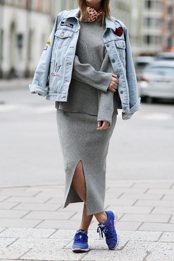 Trendy blonde in grey woolen skirt and denim patchwork jacket