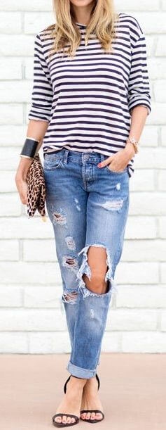 Trendy blonde in striped top and ripped boyfriend jeans