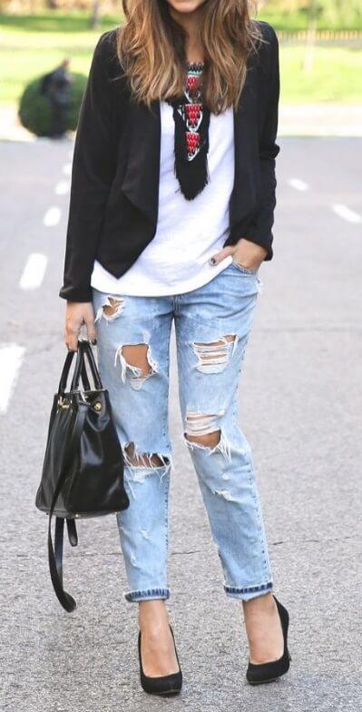 Trendy brunette in black blazer and ripped boyfriend jeans