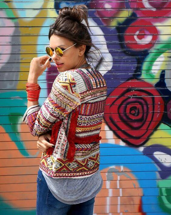 Trendy brunette in blue jeans and bright patchwork jacket