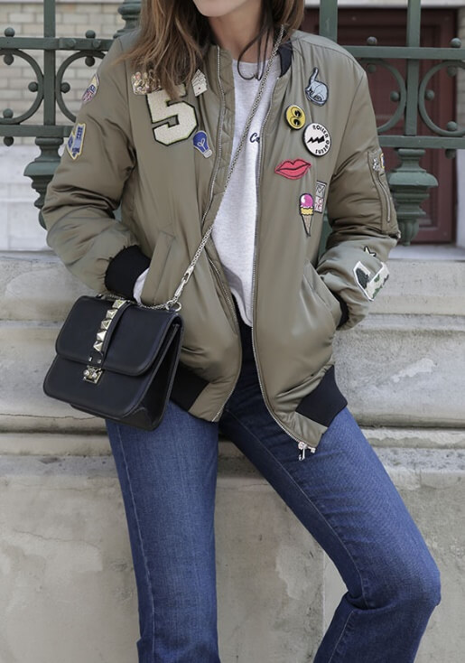 Trendy brunette in blue jeans and olive-green patchwork bomber jacket