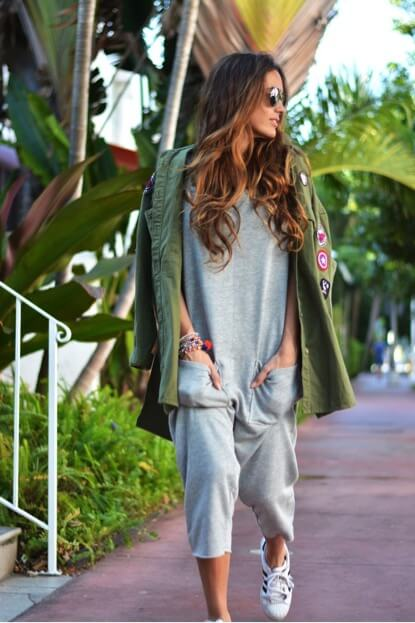 Trendy brunette in grey jumpsuit and olive green patchwork jacket