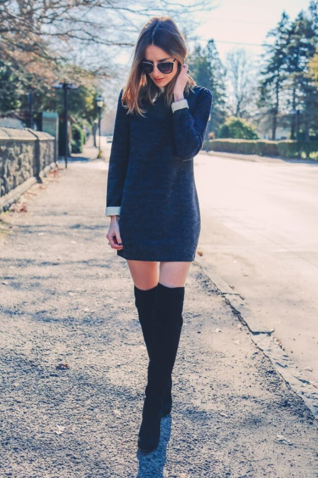 Trendy brunette in navy blue sweater dress and black thigh-high boots
