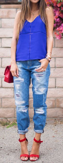 Trendy brunette in red stiletto sandals and boyfriend jeans