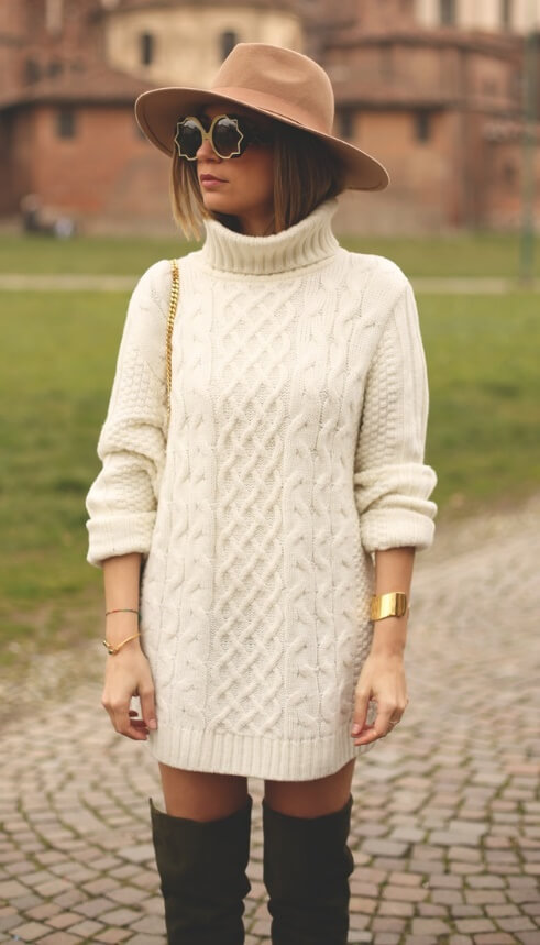 Trendy woman in cream turtleneck sweater dress, brown hat and olive green boots