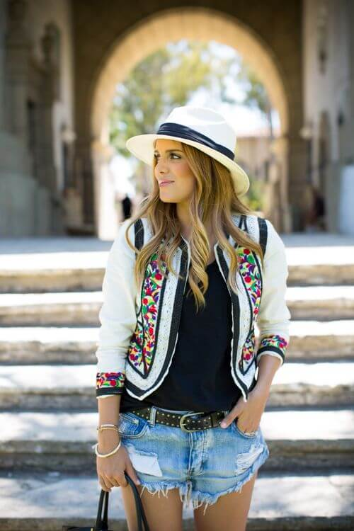 Trendy woman in cut-off denim shorts and white patchwork cardigan