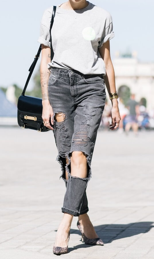 Trendy woman in grey boyfriend jeans and pointy stiletto heels