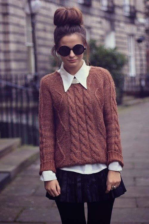 Preppy woman in brown woolen sweater and pleated woolen mini skirt