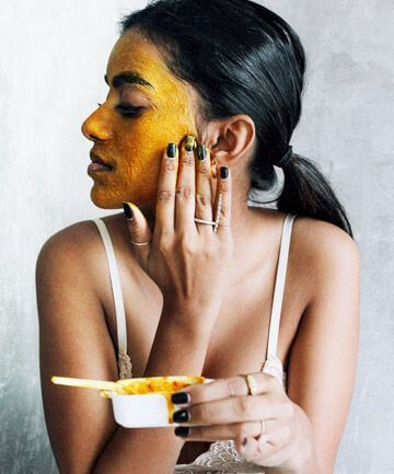 Woman applying turmeric paste to face