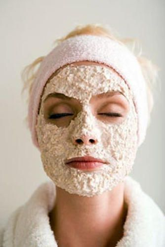 woman in a bathrobe with an oatmeal mask on her face