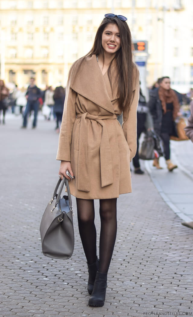 Woman wearing a camel coat with sheer tights and black ankle booties