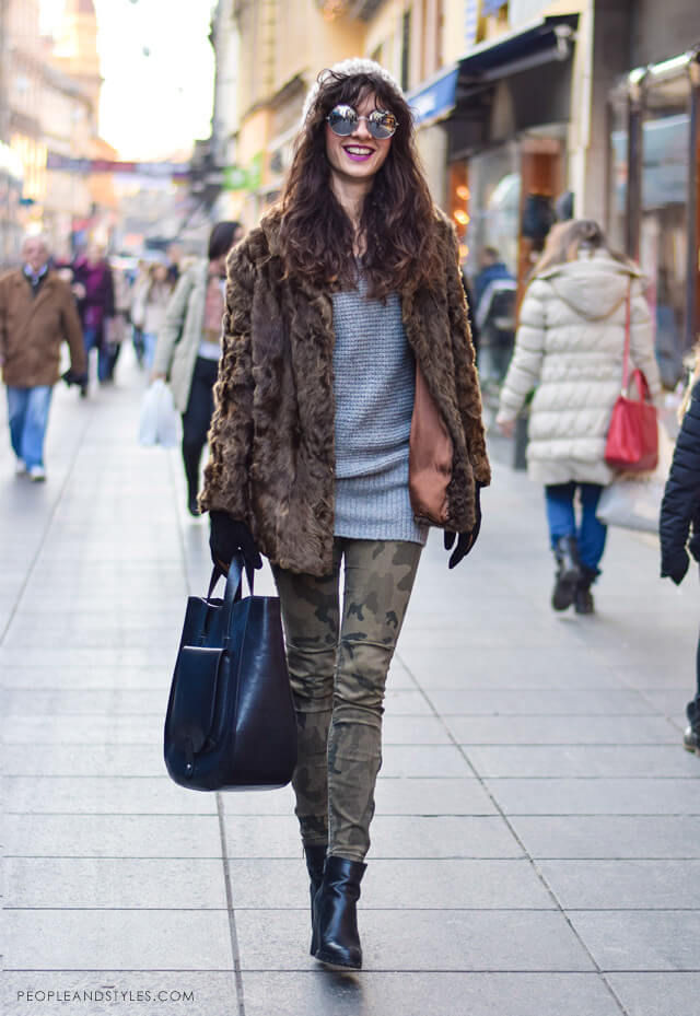 Woman wearing a grey sweater, military print jeans, ankle boots and a fluffy coat