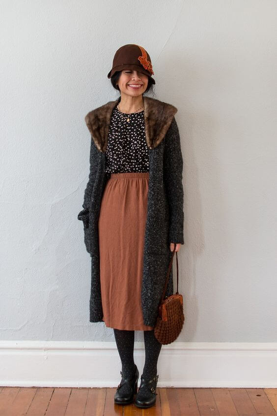 Woman wearing a polka dotted top, rust colored midi skirt, long coat, and a 20s-style hat
