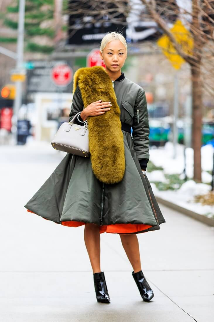 Woman wearing a statement coat faux fur and patent ankle boots.
