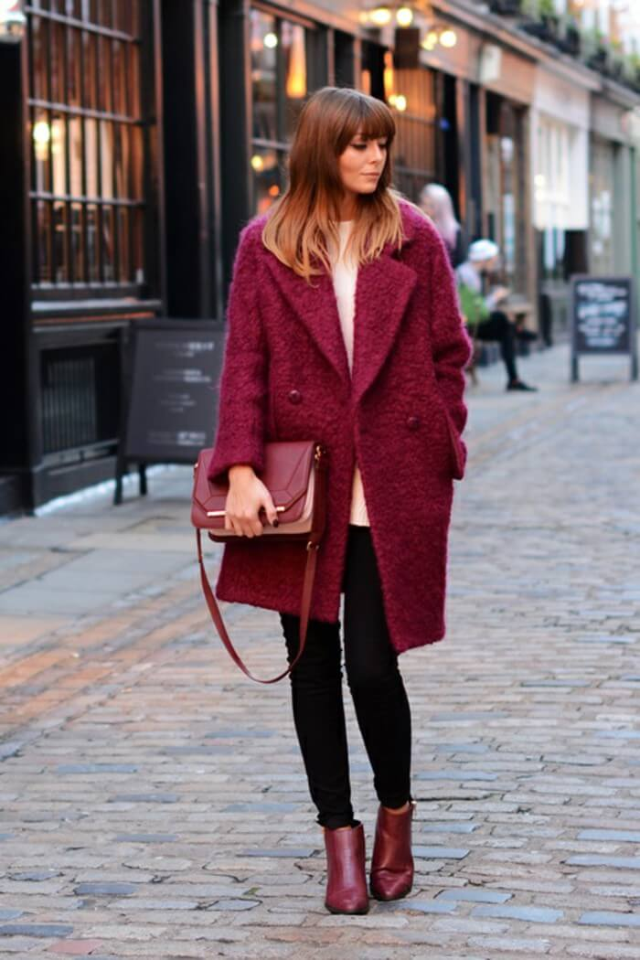 Woman wearing black jeans with a maroon coat and matching boots and bag