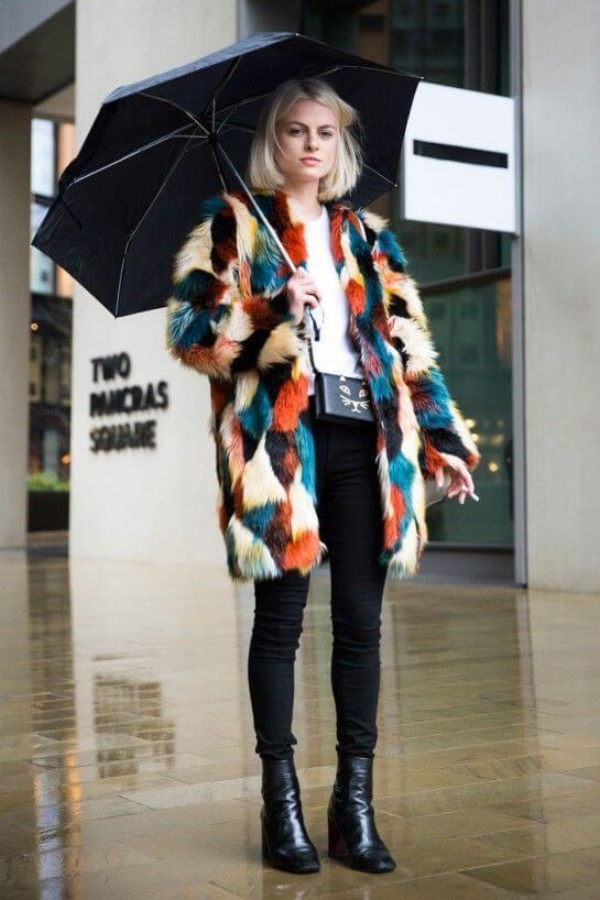 Woman wearing black pants, white tee, and a colorful coat