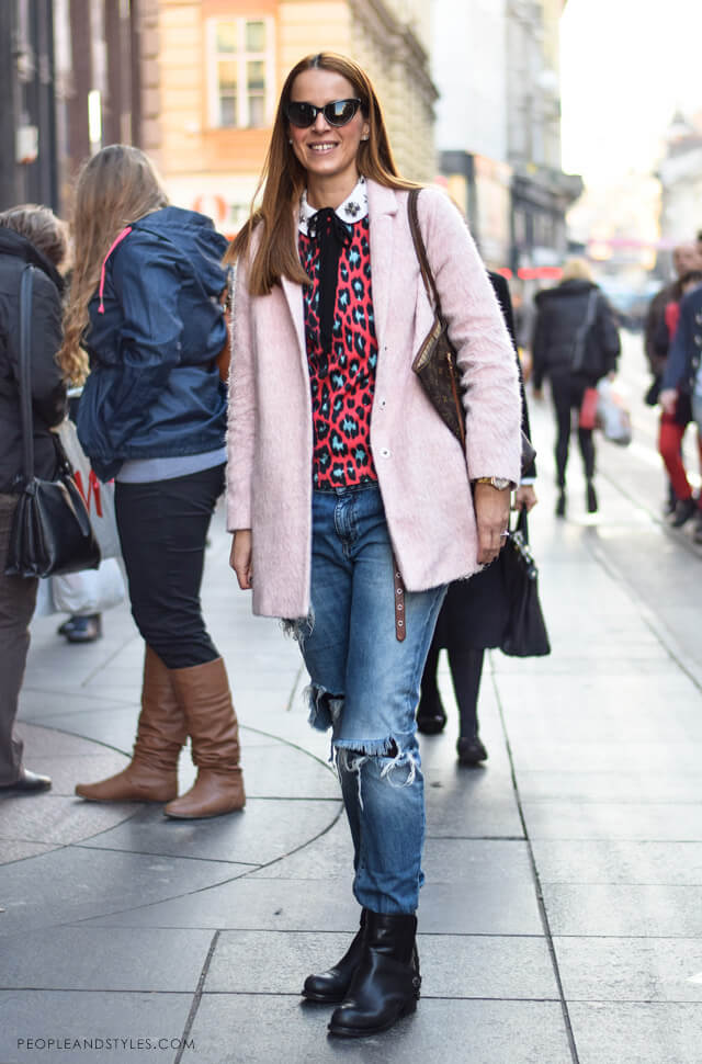 Young woman wearing a neon animal print top, boyfriend jeans, blush pink coat and black ankle boots
