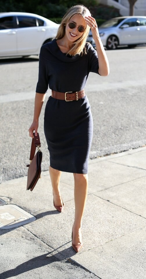 Chic blonde in navy blue sweater dress, brown belt, and brown heels