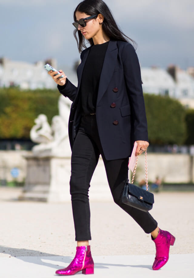 Woman in black jeans, black top and navy blue jacket with fuchsia ankle boots