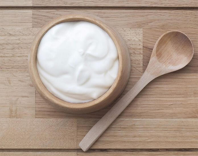 Wooden bowl with yogurt on a table