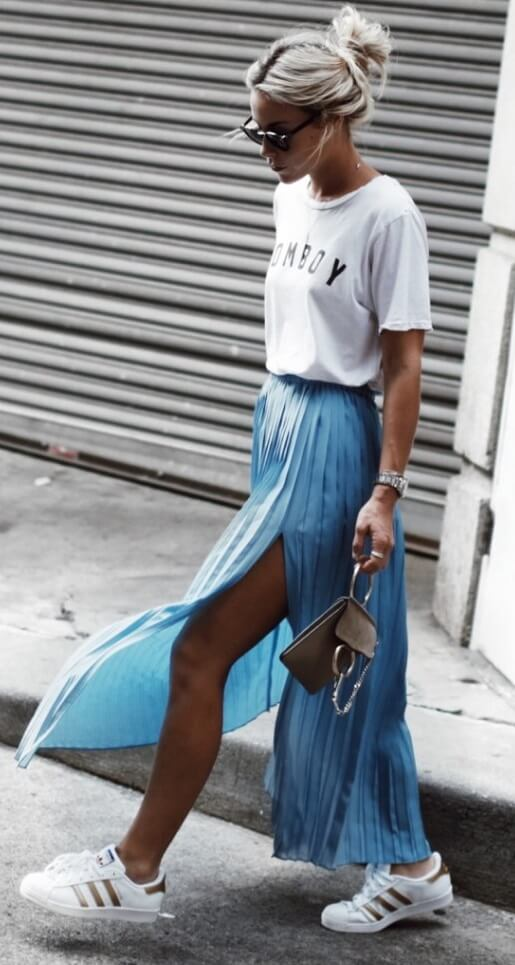 Trendy blonde is wearing a turquoise pleated maxi skirt and Adidas Superstar trainers. Why not inject some spring fever into your look with a splash of mermaid blue?