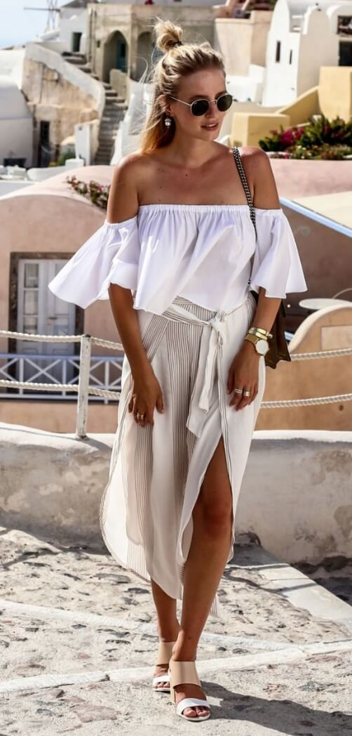 Stylish blonde on holiday wearing a white off-the-shoulder bell sleeve top and linen pants. Get into the holiday spirit in loose fabrics of pure white and crisp neutrals.