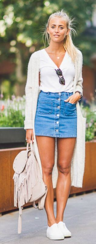 Trendy blonde is wearing a button-down denim mini skirt and white trainers. This casual daytime look captures the fresh youthful spirit of spring.