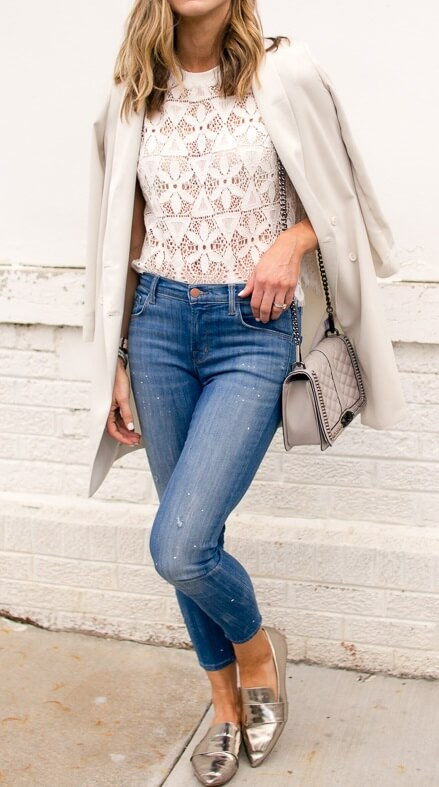 Stylish blonde is wearing a white lace top and skinny blue jeans. White lace lifts basic blue jeans into a chic ensemble every time.