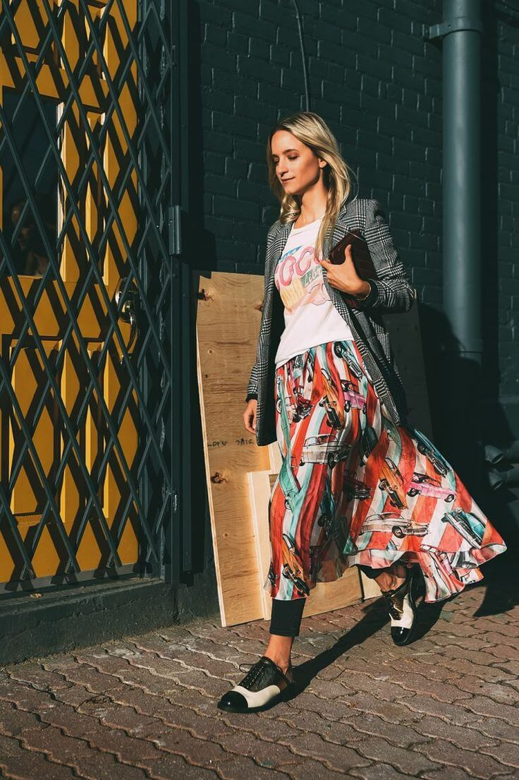 Walking blondie with long printed skirt, t-shirt and open black and white blazer