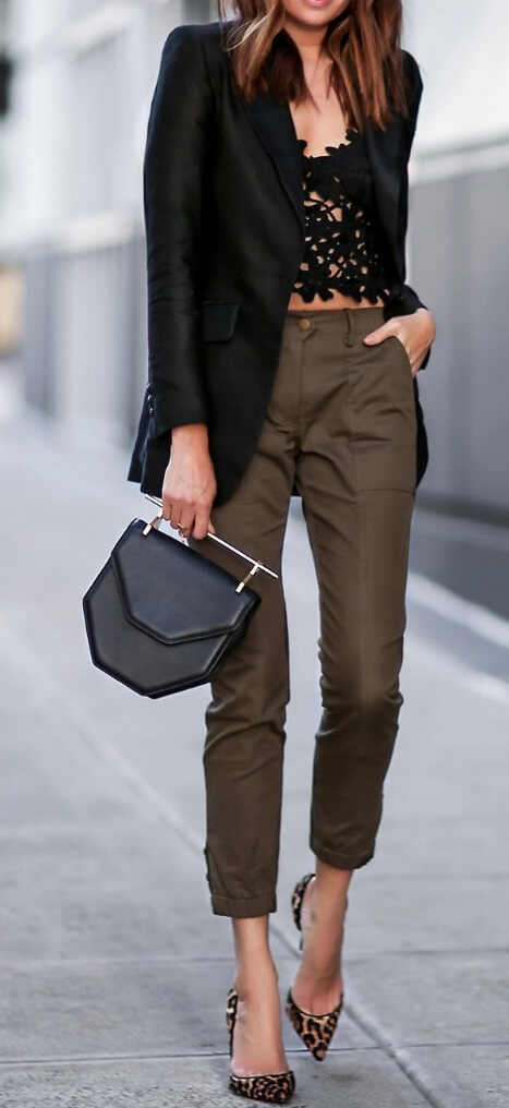 Edgy brunette is wearing a black lace cut-out top and olive green pants. Put a spin on spring's pastel shades by going for a darker, more daring motif.