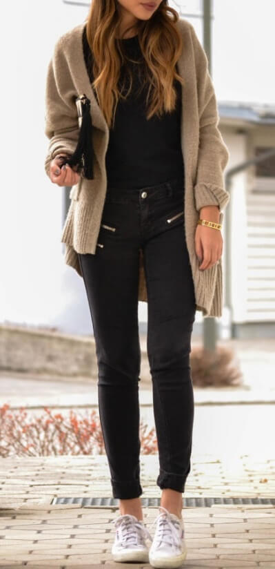 Stylish brunette is wearing black pants and an oversized woolen cardigan. Winter favorites will see you cozily into spring when the weather hasn't warmed up yet.