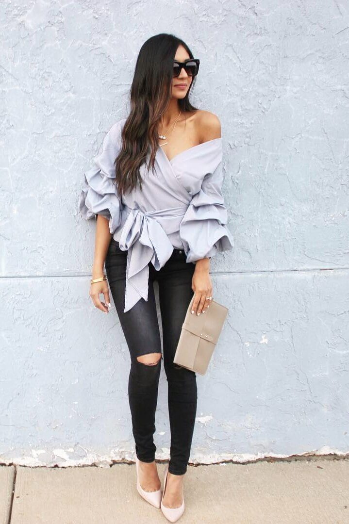 A brunette in ripped leather pants and a ruffled bell sleeve blouse. Ruffles are back and ever so chic, especially when worn with edgy leather pants.