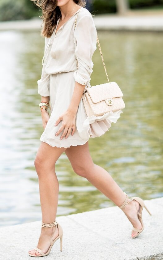 Stylish brunette is wearing a silk chiffon dress and Steve Madden heels. A monochrome palette of soft nude shades gives a soft edge to a spring day.
