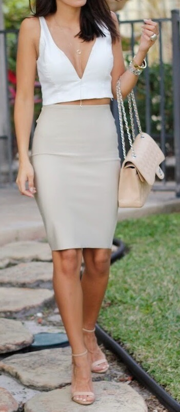 Stylish brunette is wearing a nude pencil skirt and a white V-neck crop top. Indulge your sophisticated side by opting for sleek, slim-fitting basics in neutral shades.